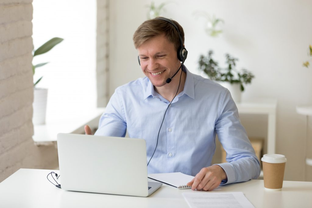 Smiling young businessman wearing headphones and looking at a computer screen with a takeaway coffee beside him on the desk planning sustainable travel programs