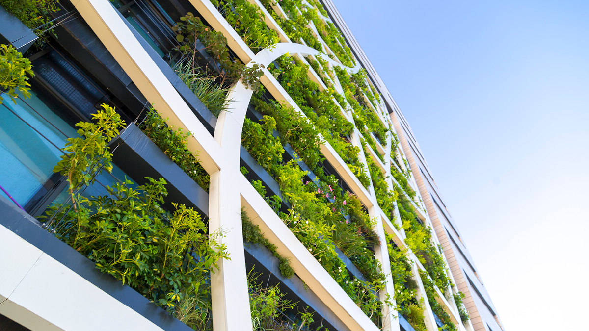 The façade of a sustainable modern hotel covered in leafy green vegetation.