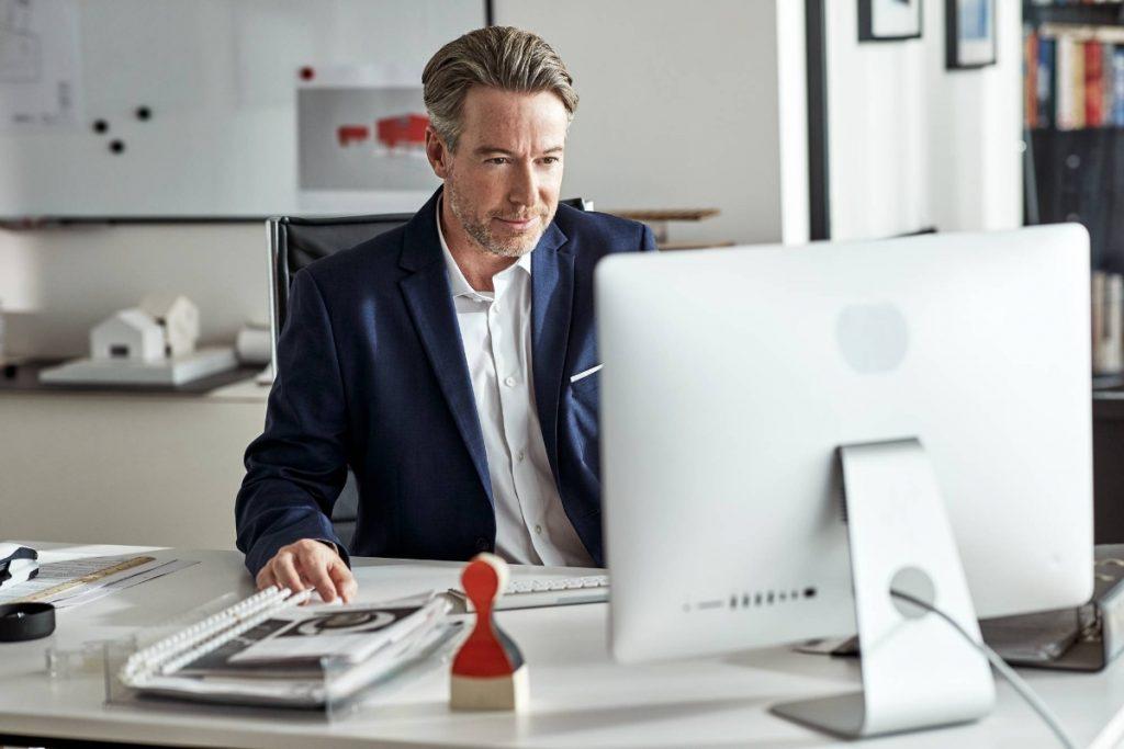 Ein Geschäftsreisender informiert sich zu HRS Rebooking an seinem PC.