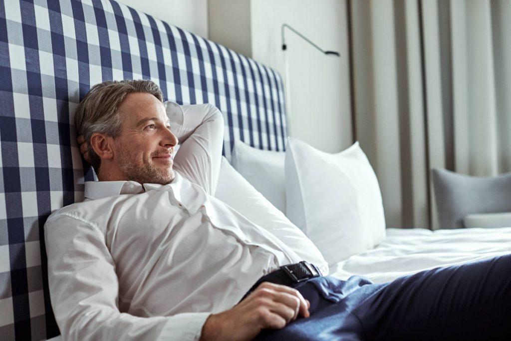 Ein Geschäftsreisender liegt auf dem Hotelbett und genießt seine Reise aufgrund von HRS Rebooking.