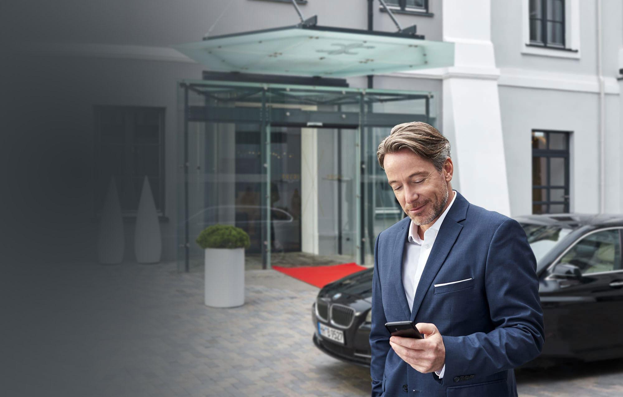 HRS Rebooking läuft einfach im Hintergrund: Ein Geschäftsreisender steht vor einem Hotel und schaut auf sein Smartphone.